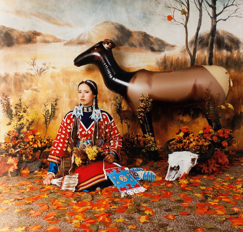 Native American woman in traditional dress kneels on floor surrounded by artificial and natural props: inflated elk, dried flowers, buffalo skull, and colored leaves; painted landscape backdrop