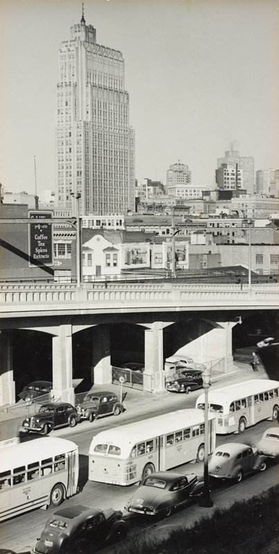 view of city street and overpass, with cars and busses; high rise buildings at top