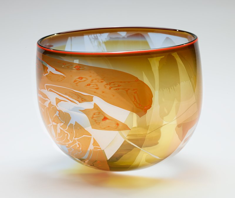 deep bowl with rounded bottom; wide rim; clear glass with yellows, orange, blue and white; etched design of two women, with standing woman holding a rabbit; large white and blue rabbit's head; abstract colored patterns