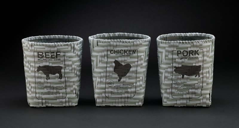 """woven basket with square bottom made of strips of grey paper; strips printed on front of basket with a label reading """"PORK WITH JUICES"""" and other text and silhouette of a pig"""
