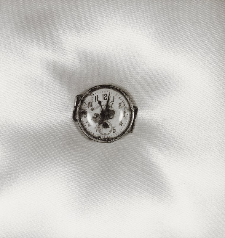 damaged wristwatch without a band against light-colored fabric background