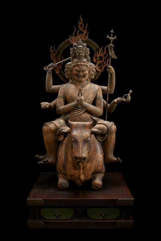 "figure with six heads, arms, and legs astride crouched bull on wood base; metal bands around wrists, some biceps, and most ankles; halo with flames attached at back; two hands of two arms together in praying position, other arms bent and flare outwards. Upper left arm holds long staff, lower one holds implement with ""curly q""-shaped end. Upper right arm holds a trident. Lower right arm fingersshaped like it was holding something in hand. Three bottom heads have crystal inlay eyes. Three smaller heads on top considerably smaller."