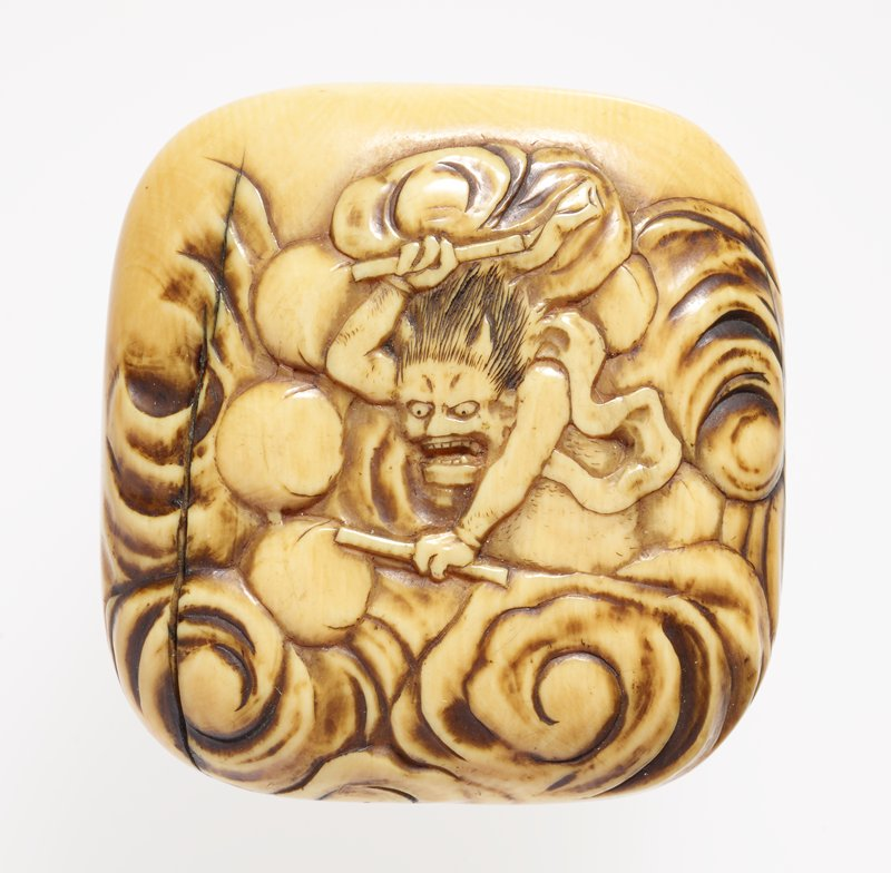square shape with carved raijin figure amid swirling clouds; raijin wears a fierce look, and brandishes drumsticks above and below face