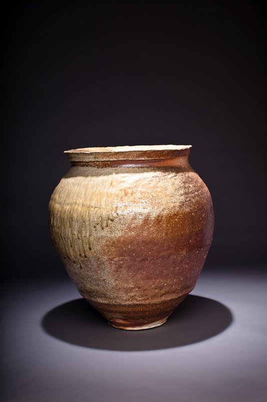very large stoneware vessel with wide mouth, thick lip; swells at midsection and tapers toward base; rust colored and beige glazes