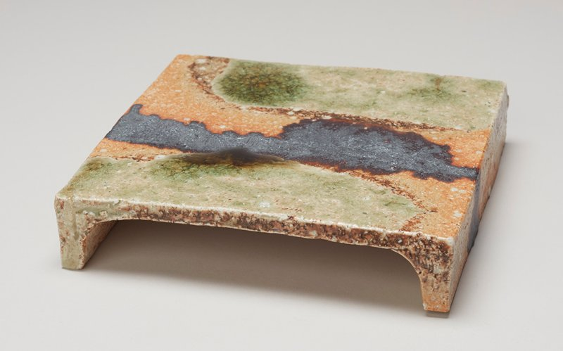 flat square plate with two feet running the length of two sides; reddish-tan base glaze with irregular stripes of green flanking a stripe of dull grey