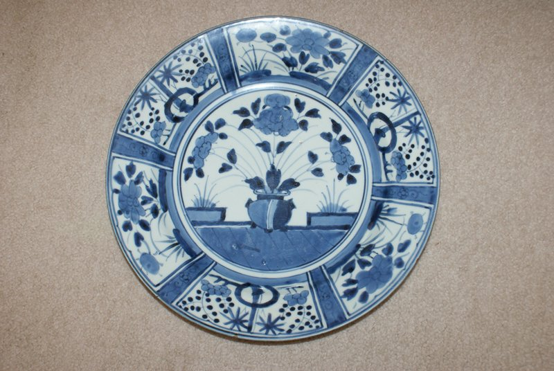 blue and white; foot ring; rather wide sloping rim; white on bottom; center decorated with image of rounded vessel with three large flowers; rectangular cartouches on rim decorated with potted plants and flowers