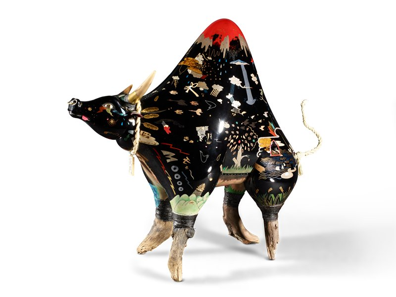 black lacquer bull with mountainous hump with red tip rising from back; bull is decorated with various vignettes of trees, plants, clouds, animals, and people; belly painted with brighter colors; pink leather tongue sticking out of mouth; wooden legs; detachable rattan tail
