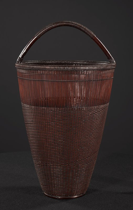 fine weave basket with raised loop handle; body tapers toward base; weave more open at top section with only vertical strands