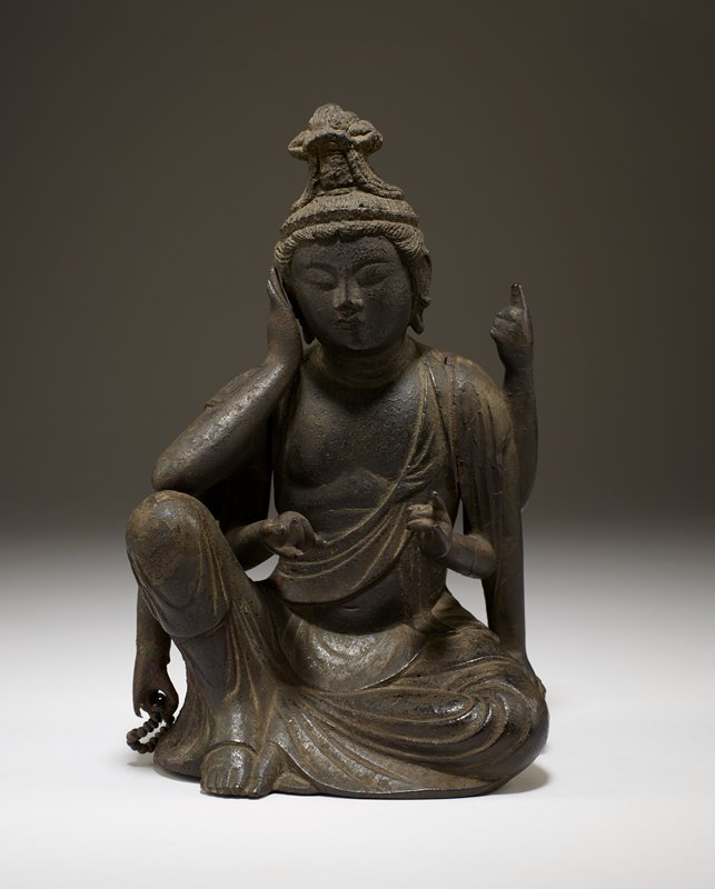 "figure seated with one knee up; six arms; of PL arms: one pointing up, one placed on ""floor"", one outstretched in mudra; of PR arms: one placed next to cheek, one down and holding bracelet, one outstretched holding sphere"