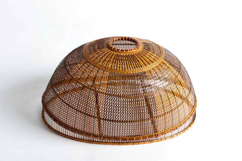 oblong dome rising up to narrow, circular opening at top; open weave background with very narrow rattan strips forming crisscrossing pattern; vertical tan and black strips overlaid and woven in at horizontal bands; two horizontal support bars on bottom