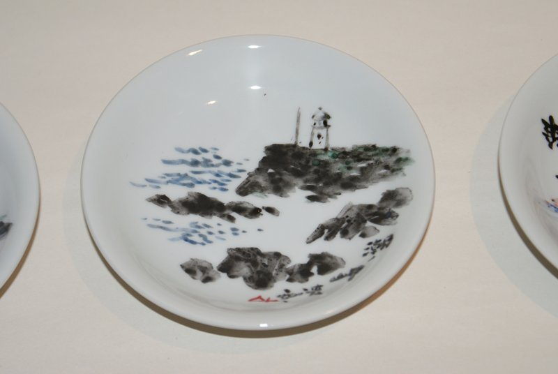 small dish with image of lighthouse on black rock; other black rocks at R; water at L; inscription bottom