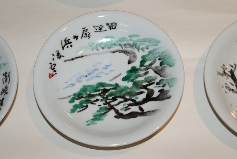 small dish with painted image of bay; green trees surround bay on three sides; hints of blue waves at center
