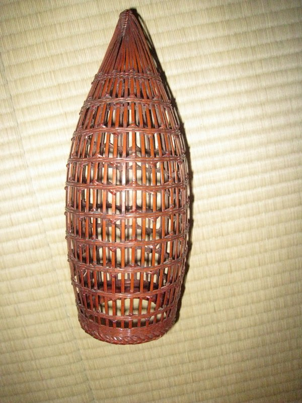 rounded, cone-shaped hanging basket; open, vertical weave with spiraling horizontal supports; subtle, zigzagging detail around supports; bamboo inner cylinder