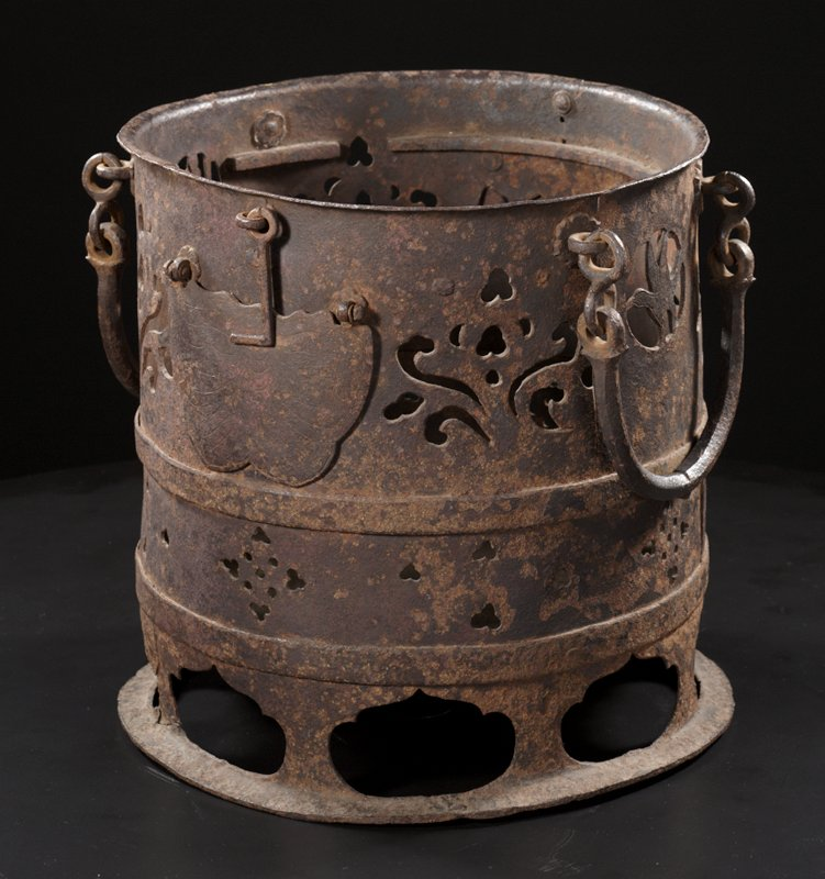 a: round iron vessel with semi-circular handles hanging on each side; bird in open circle below one handle and standing creature with shovel (?) in open circle below other handle; openings cut out in organic shaped designs on body; L-shaped hooks attached to each side to hold open doors; wing-shaped doors below that lift upwards, attached with two hinges; incised decoration on each door; solid bottom inside that is raised from very bottom with openwork around base in oval forms with points at top of each; b: brass insert with wing-shaped opening on each side; c, d: open brass handles