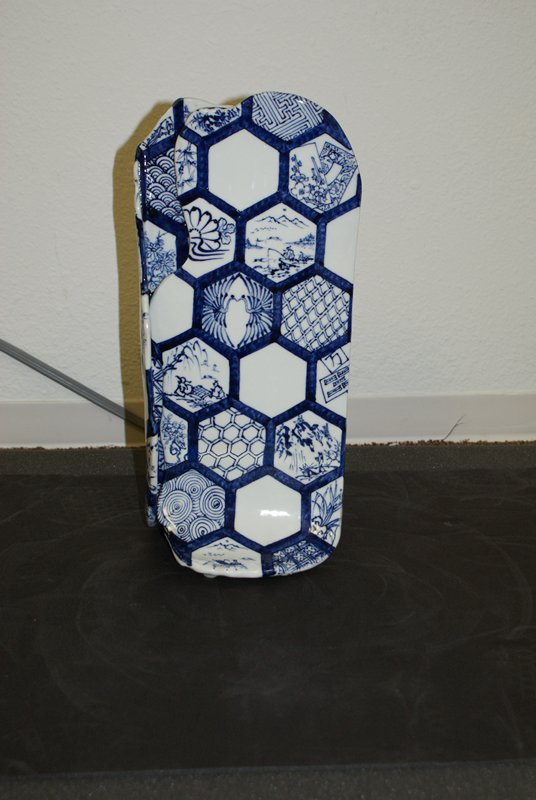 two irregular vertically oriented slabs, interlocking at sides, with flared base; blue honeycomb pattern with blue and white vignettes