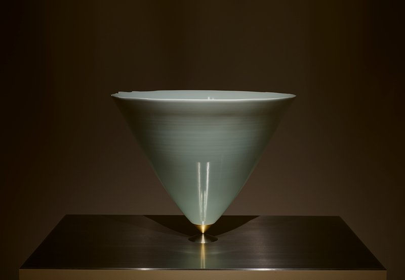 open top upside down conical shape of pale blue porcelain that tapers to tip that is covered in gold colored metal; screws into flat conical stainless steel piece; centered on flat stainless steel plate base