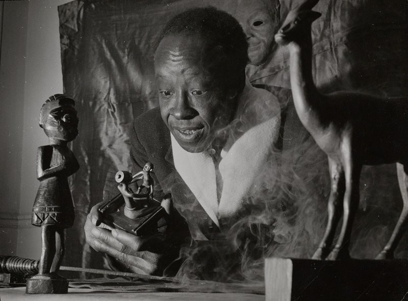 black man with raised eyebrows looking intently at a mother and child figure held in both hands; African sculptures of an animal at R and a figure at L; smoke on R side of image