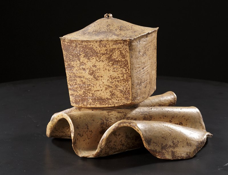 cube like stoneware form resembling small hut seated on wavy stoneware form; tan and dark brown glaze