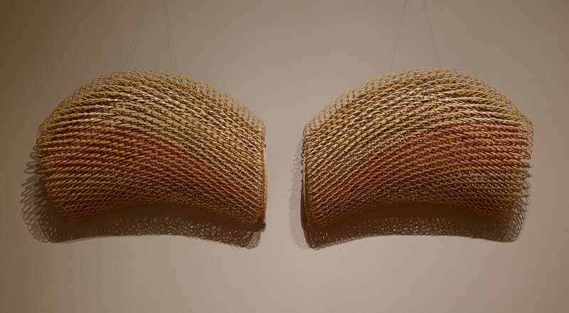 two pieces of almost semi-circular form covererd with raised loops of bamboo all going horizontally; most of bamboo light in color with wide strip of slightly redder bamboo across center of both