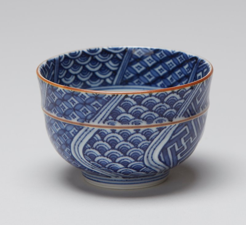 tea cup with blue and white patterns separated by three vertical bands of blue and light blue; horizontal raised band around top in brown; brown lip