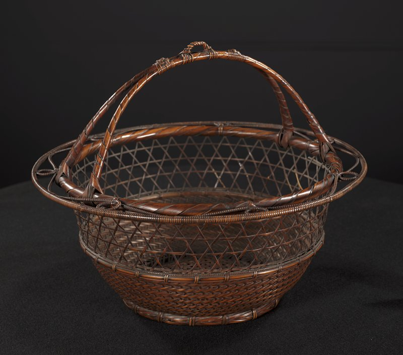 round basket with decorative ring around mouth featuring woven circles and waving line; 2-pronged handle with two decorative knots flanking hook at handle's center; closed weave around bottom half; large, open, star-patterned weave upper half; rich, purple cord with copper hook attaches to basket; copper pan