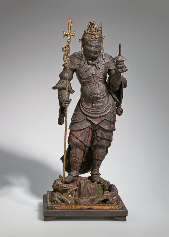 standing figure holding staff in PR hand and miniature pagadoa in outstretched PL hand; he is wearing elaborate crown and armour; figure attached to base with keys on the bottom of the feet; staff is removable