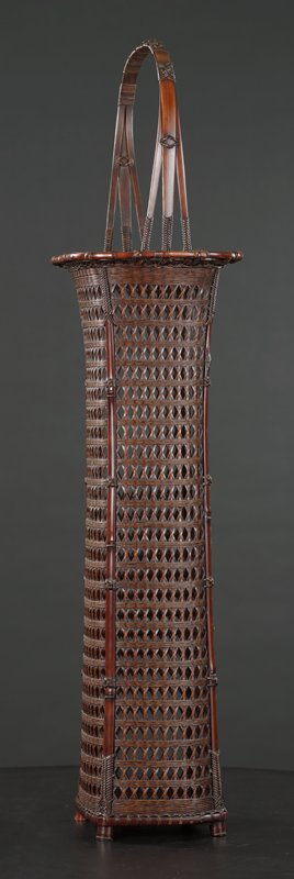 very tall, towering, four-cornered basket with flared top; open, diamond-patterned weave with layers of woven horizontal cross-pattern; handle made from three thin bamboo strips that join at the top, secured with a row of decorative knots; handle separates into three strips at basket lip, adorned with decorative weave at base; tall, red-brown bamboo cylinder lined with copper