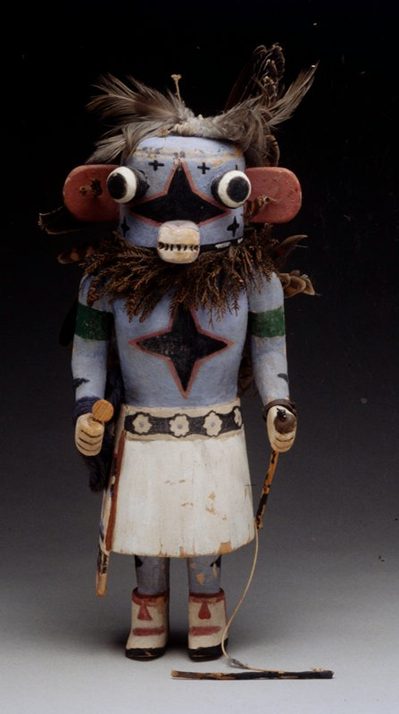 carved wooden doll painted blue, with white skirt, red ears, feathers up back and on top of head; black belt with white flowers that have a blue center; foliage around neck, on PL hand figure is holding stick with string attached to another stick that was perhaps attached at one point; blue yarn around PR wrist; metal ring around PL wrist with teal green stone.