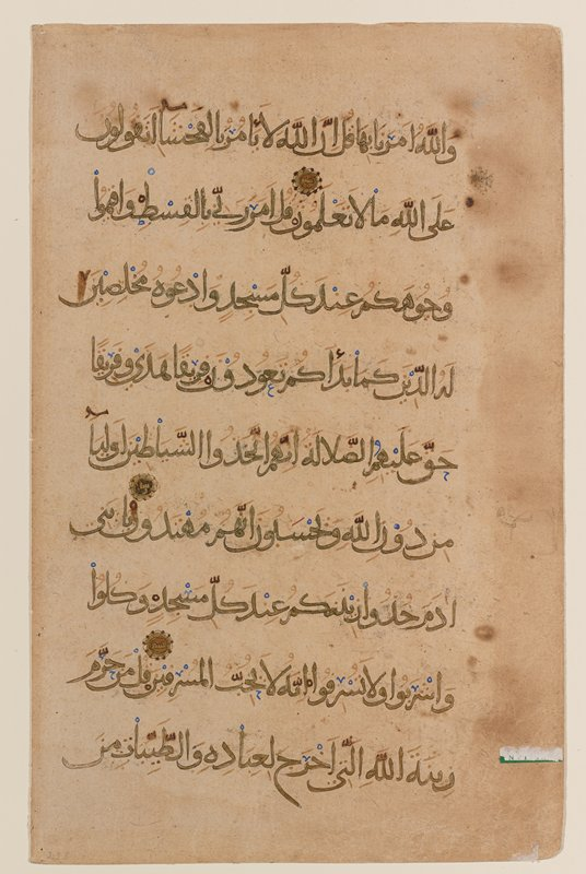 Text from Sura 7 from the Koran. Vertical paper with nine lines of gold Neshki with thin black outlines to a page. Vowels and diacritical marks in red, reading marks in blue and black. The text is from Sura 7, starting in the middle of verse 23 and ending on the next page in the middle of verse 30. The gold rosettes indicae the end of a verse and give its unit number. The marginal decoration is the imprint of the decoration on the opposite page, marking the end of the twentieth verse.