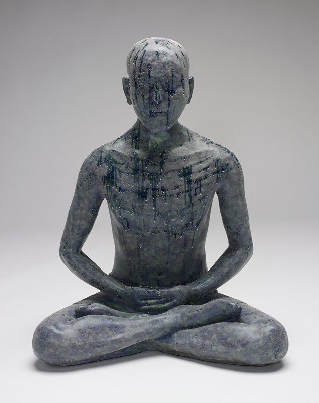 figure slightly smaller than life size, seated cross-legged with hands one of top the other in lap; eyes closed; mottled green glaze with silver liquid-appearing beads and drips overall