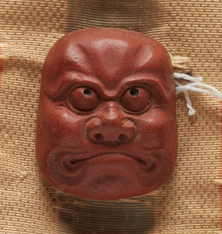 netsuke in the form of a mask; red clay; frowning face with wide cheeks; wide nose; bulging eyes, looking up; thick brow; lines around mouth; 2013.29.1217.1-6 received attached to patterned orange, cream and blue ribbon (ribbon in poor condition--shredded)