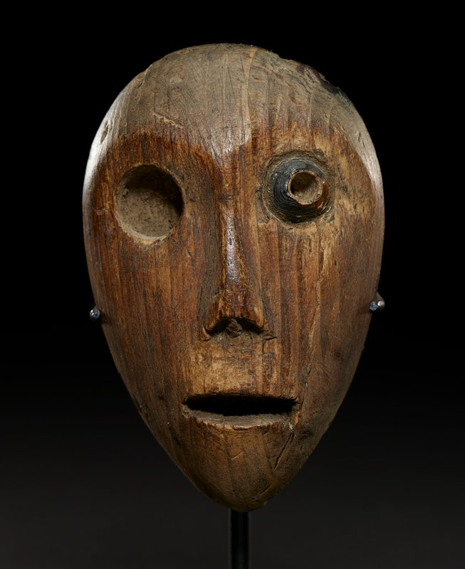 rather flat, teardrop-shaped face; open, horizontal mouth; long, flat nose; round eyes; PL eye has round inlay (possibly shell or ivory); PR eye is missing inlay