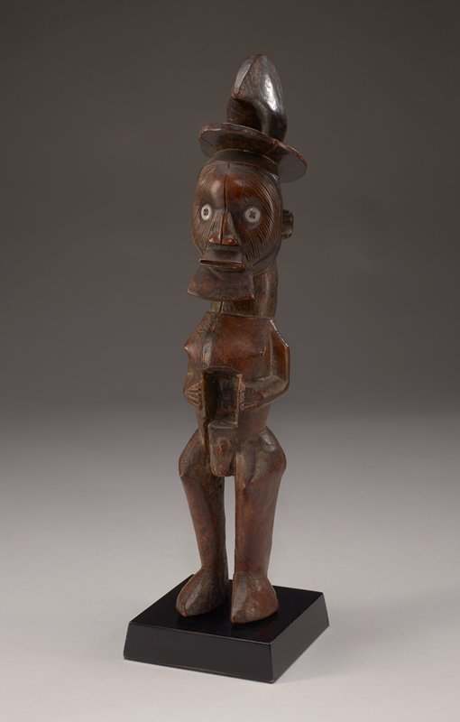 standing male figure wearing hooked hat/headgear with flat brim; eyes are white buttons; deep rectangular cavity in abdomen; wide, flat nose; vertical scarifications on face; wide mouth with thin protruding lips; wedge-shaped beard (?); medium wood tone; attached to black base