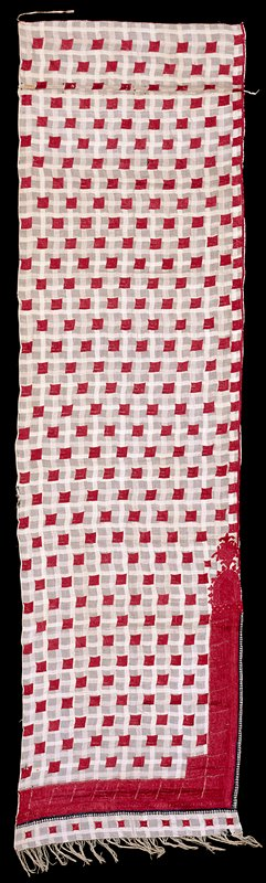 sheer white fabric woven with plaid design; embroidered overall with isolated red squares; PL side has border with squares and large organic motif near LR corner with solid red embroidery at corner and bottom; black embroidery around solid red section; fringe at bottom with row of red squares above. Surface ornamentation (Needlework)