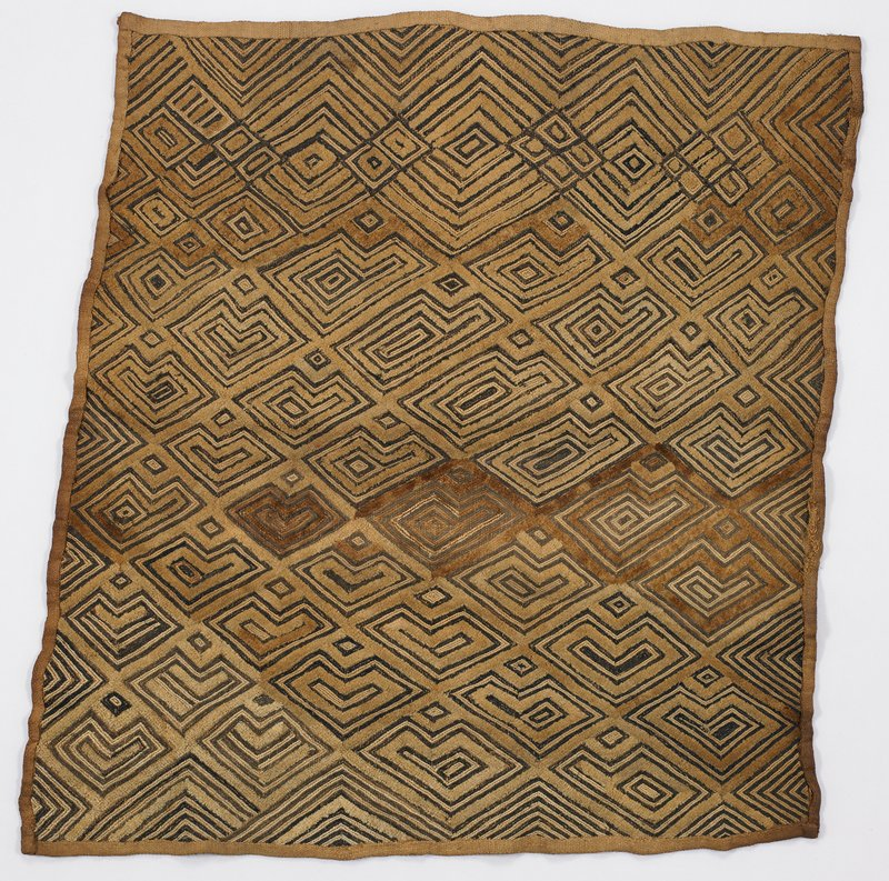 Tan clothwith P and L-shaped designs in dark fiber; zigzags and diamonds at one end; area of darker pile near center