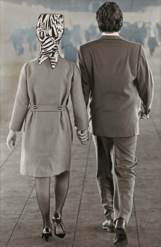 couple seen from behind, walking, holding hands; woman at left wears a coat, low heels and a black and white patterned head scarf; man at right wears a medium-toned suit; blurry figures (?) in background
