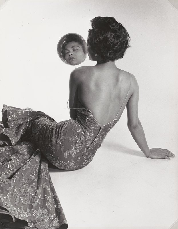 dark skinned woman seen from back, with short hair, wearing spaghetti strap mermaid dress with floral patterning, with PL strap falling off her shoulder, seated on floor; woman's face visible in round hand mirror over her PL shoulder; white ground