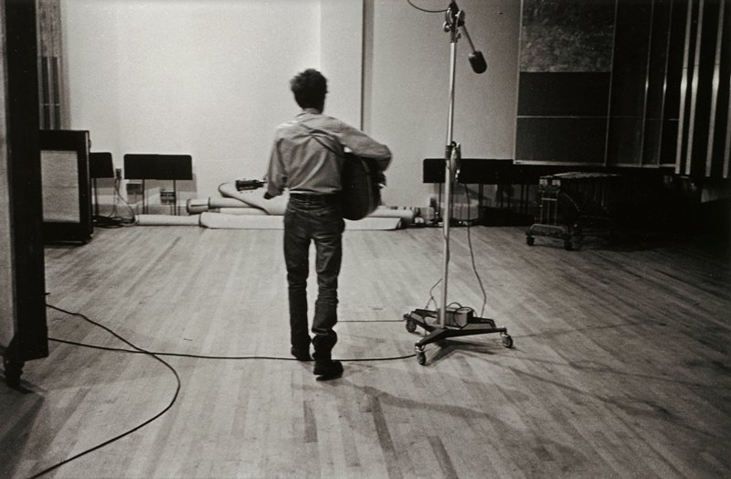 man, seen from back, with bushy hair, wearing blue jeans and shirt, playing the guitar, in a room with a wood floor and a microphone on a tall wheeled stand right of center