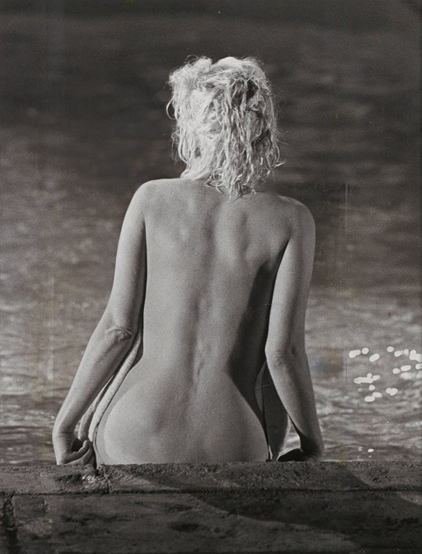 back of nude blonde woman seated at the edge of a pool
