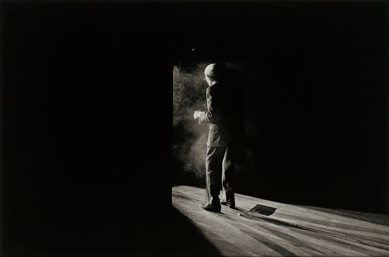 elderly man seen 3/4 from PL side, partially in shadow, with light in front of him; man wears glasses and suit; smoke in front of man