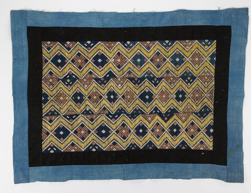 3 brocaded panels with diamond design in yellow, white, tan and blue sewn together; double border with black on interior and blue on exterior