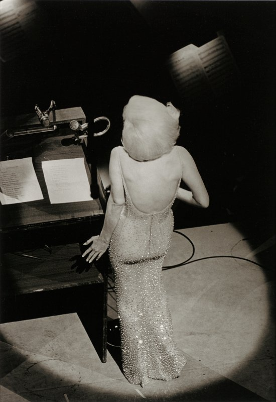 view from behind and above of woman in a backless sequined gown with blonde hair standing next to a piano with a spotlight shining on her