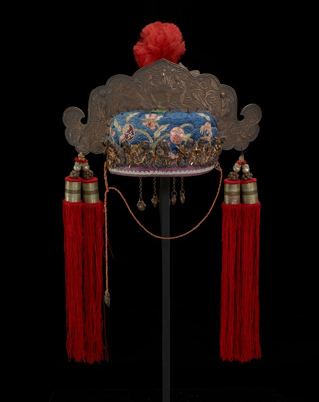 blue silk base embroidered with floral designs in multicolors; pink silk interior; nine metal figures attached to front, with dark and gold patina; four long red silk tassels; large top metal ornament with relief figures and flowers; three-dimensional metal ornament on back with dragons, flames, large red pompon and other ornaments attached with springs and dangles at bottom; metal ornament with pair of figures with four dangles with pendants; one dangle with pendant attached at back with safety pin