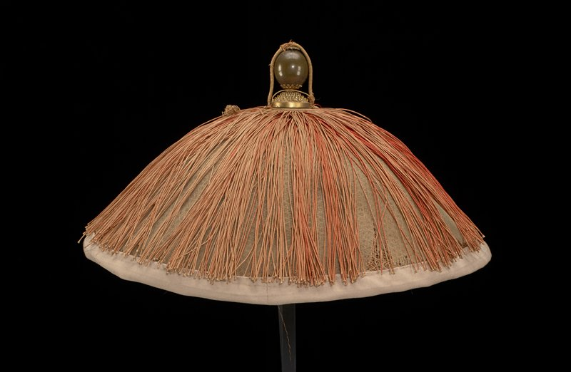 bowl-shaped; tan gauze-like cover over woven plant fiber base; tan bottom trim; top finial of metal with floral top element and openwork bottom element; silk tassels attached under finial--faded to pink; ring of paper-covered plant fibers at underside