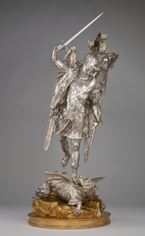 "angel wearing a breastplate and a helmet with a lion at the top and three feathers, holding a sword aloft in his PR hand; angel also wears a shield on his PL arm, printed with, ""QUIS UT DEUS""; angel wears a short skirt and a flowered sash over his PR shoulder; angel stands on a fantastic animal with a fierce dog-like head with open mouth with many teeth, lion-like body, thick tail and bat-like wings; silver figures, gilt base"