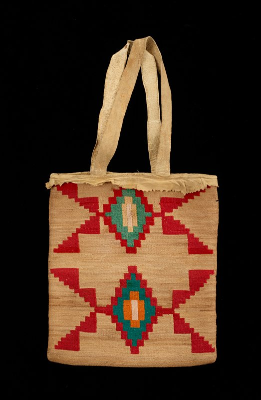 small nearly square bag with two deerskin handles and deerskin top decorative trim with zigzag edge; light tan bag with woven design on each side--one side has geometric stepped radiating diamonds, each with a pair of geometric claw-like elements, in red, greens, yellow and orange; opposite side has four star designs edged in black with yellow, light pink and turquoise