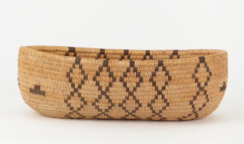 ovoid, canoe-shaped coiled basket with flat bottom; rounded sides; light brown with dark brown vertical rows of diamonds on side and three inverted T shapes at each end