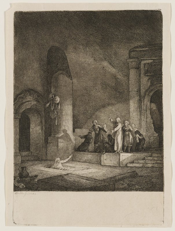 figure in white emerging from rectangular hole in ground, raising PL arm up; figure in white on raised platform with arm raised, the other gesturing toward figure on ground; small crowd of people gathered around standing figure in white; ruins in background