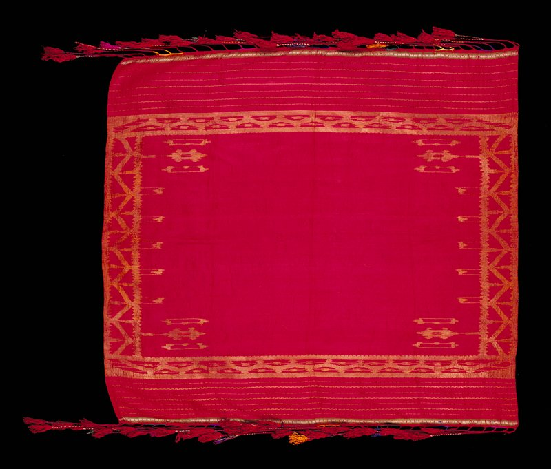 Cranberry colored with geometric designs and stripes in gold metallic thread around edges; thin green and white border above fringe on 2 sides; fringe of long strands twisted with multicolored threads. Woven fabric
