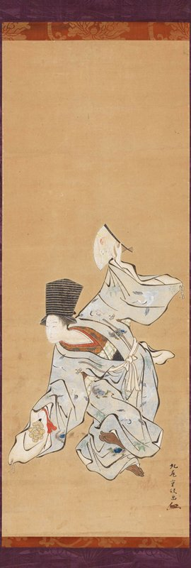 dancing female figure in light blue outer robe with crane decoration; standing on PL foot with PL leg bent across body, foot raised; PR arm down, holding bells; PR hand held up with open fan behind body; figure is looking over PR shoulder to L; tall black hat